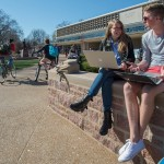 students sitting outside the library